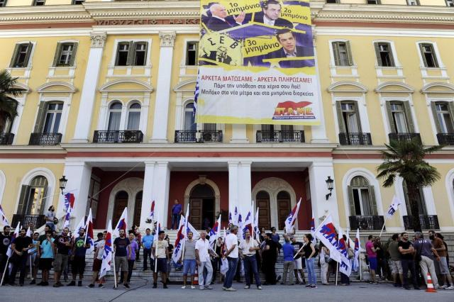 a-giant-banner-is-displayed-as-protesters-of-the-communist-affiliated-trade-union-pame-block-the-entrance-of-the-ministry-of-macedonia-and-thrace-in-the-northern-city-of-thessaloniki.jpg